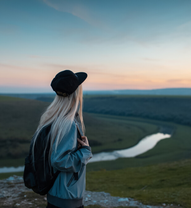 Back view of young blonde girl with backpack enjoying sunset on peak of hills. Travel concept.